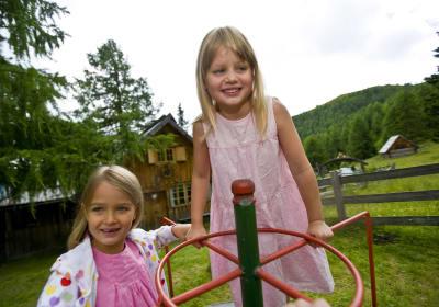 Mädchen spielen vor Hütte