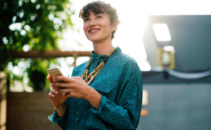Woman smiling and holding her smart phone