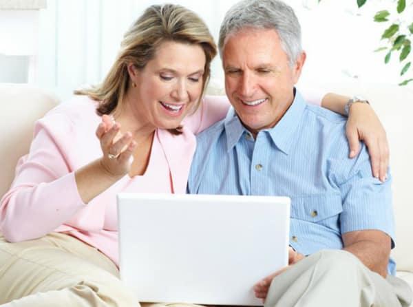 Couple qui regarde un ordinateur avec un sourire