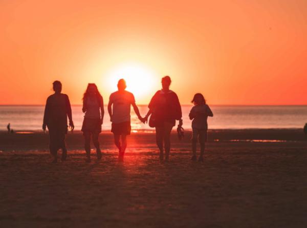 Famille sur la plage avec coucher de soleil