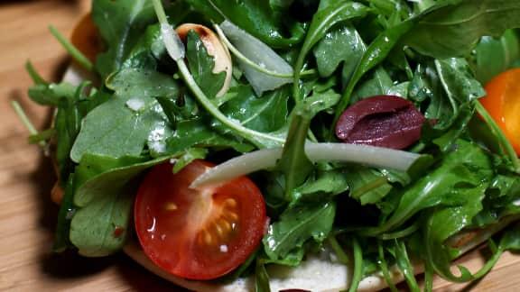 salade piquante de roquette aux olives noires sur pain plat