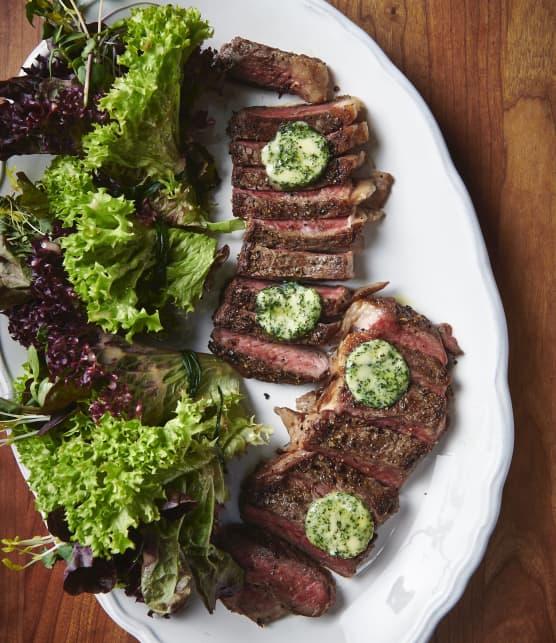 Steak de contre filet et son beurre composé aux herbes fraiches, servi avec un bouquet de jeune laitue et sa vinaigrette