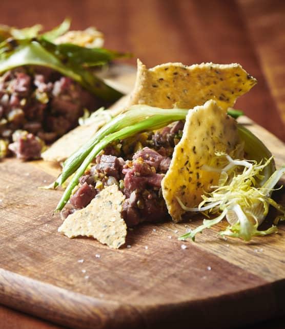 Tartare de mi-cuit de canard, olives, oignons verts grillés et tuiles de chanvre à l'estragon