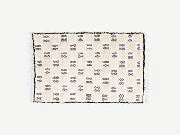 Beige wool rug with a fine black checkered pattern.