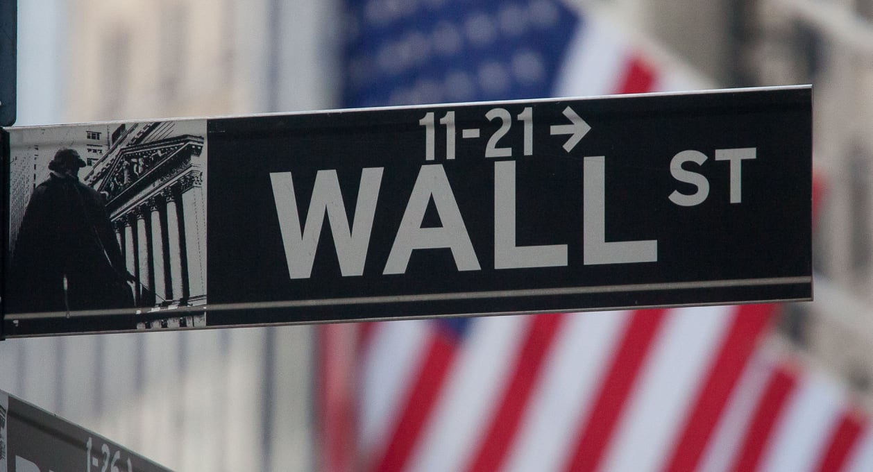 Wall Street sign with American flag in background, New York, Finance, US Finance, Financial Services industry