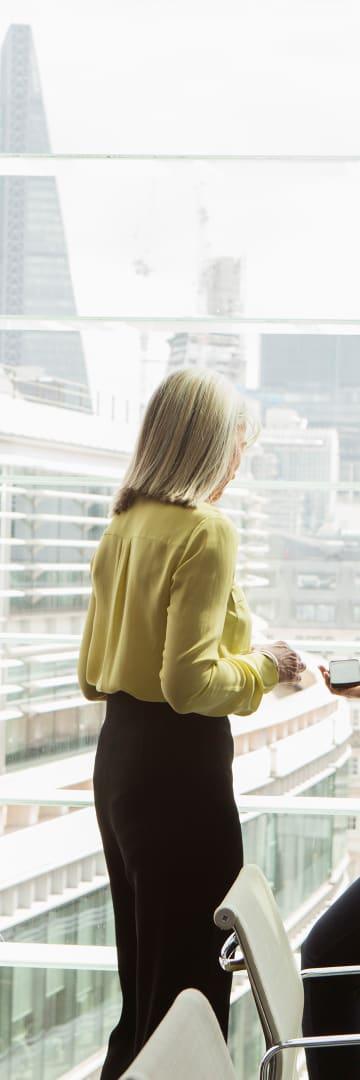 Business women talking by window overlooking London city