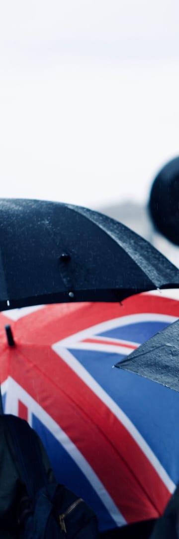 Pedestrians in rain in the UK, one with a UK insignia umbrella