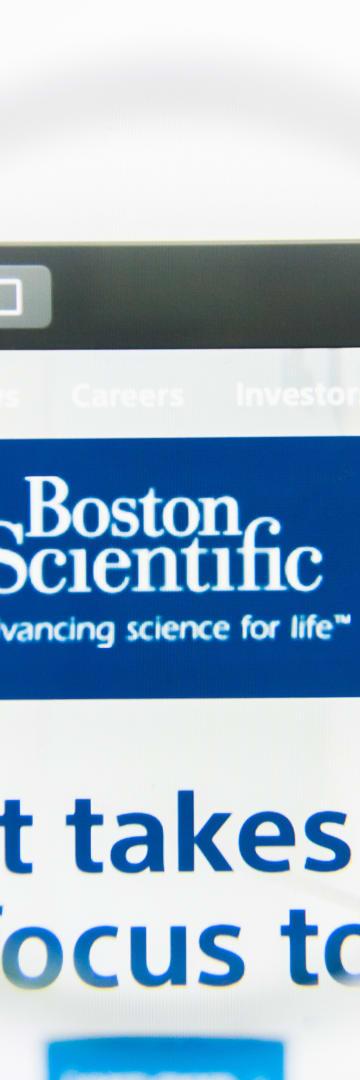 Boston Scientific logo through magnifying glass, pharmaceuticals
