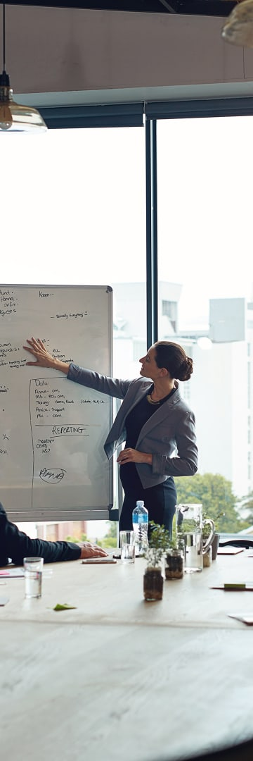 Businesswoman presenting on white board at meeting