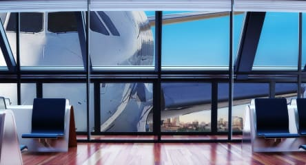 Airport waiting area with view of jetliner through windows.