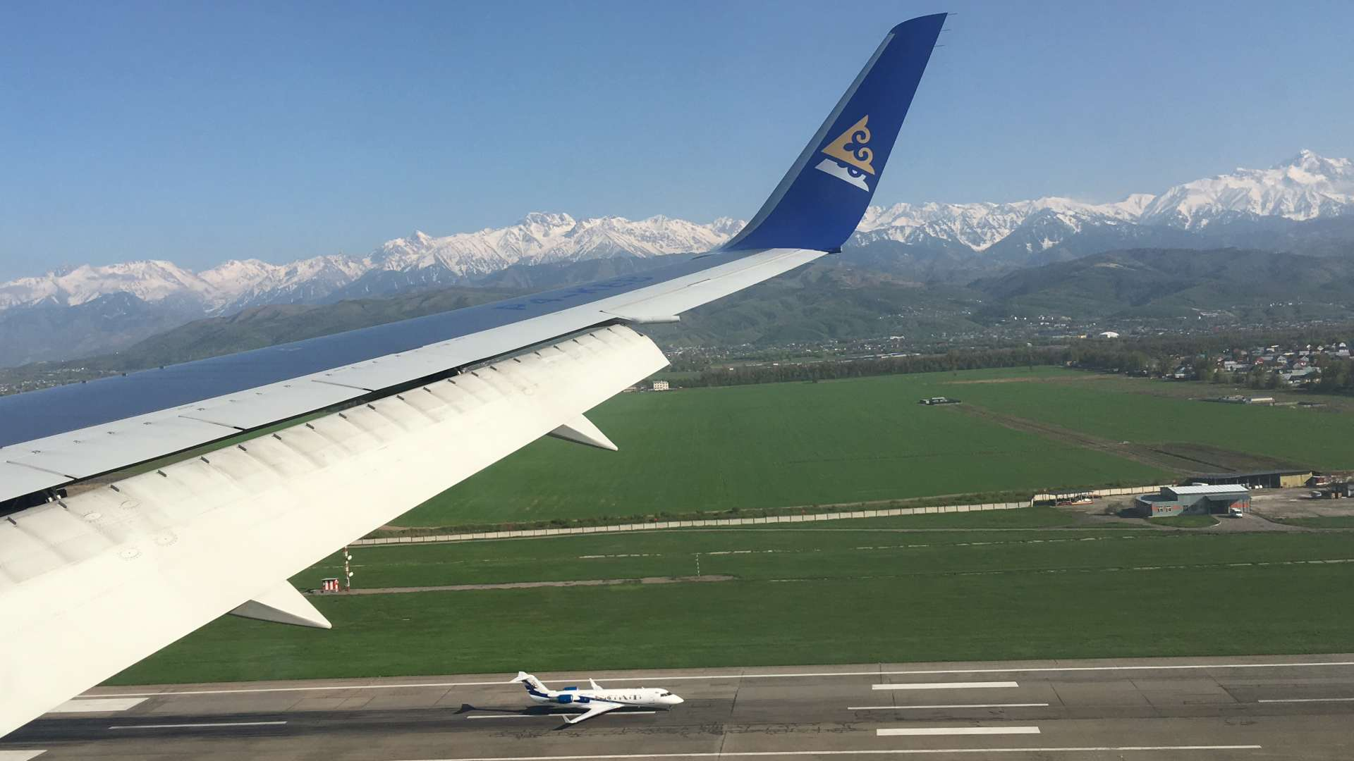 Air Astana landing in Almaty, Kazakhstan, with Alatau Mountains in the background