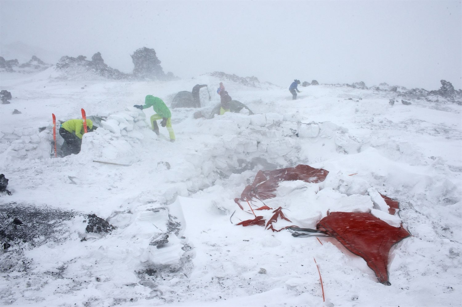 Everyone busy in camp trying to repair the snow walls. The left overs of Julia and Warwicks tent. Photo courtesy of Martin Hartley