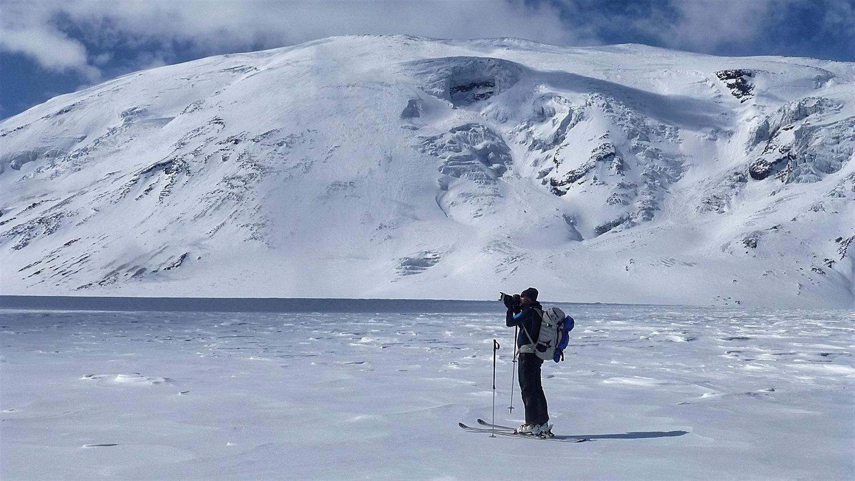 Martin taking a photo with volcano Ushkovsky behind him