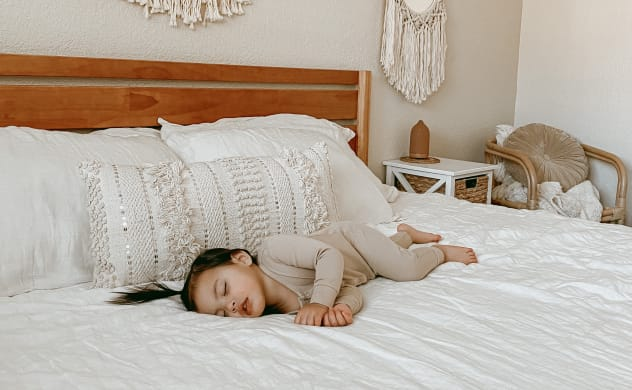 child sleeping on bed