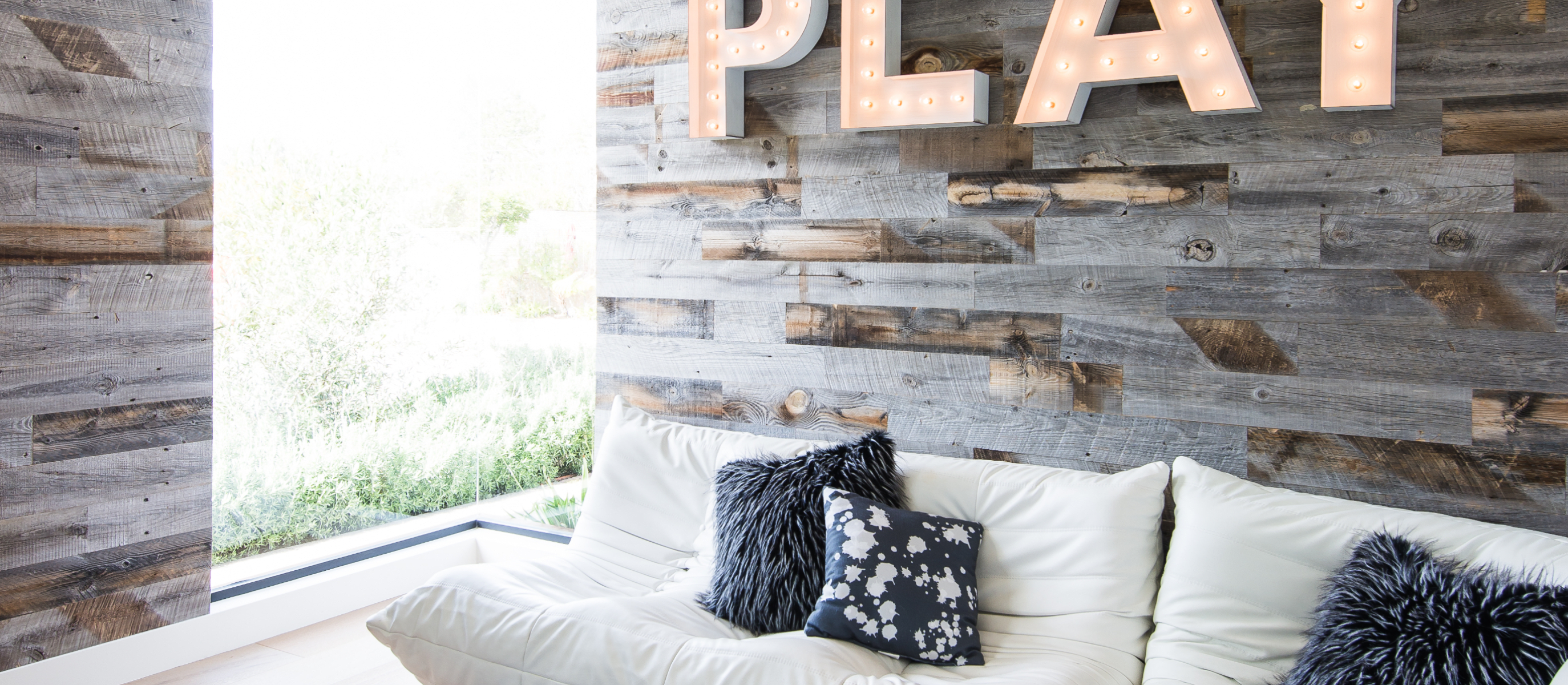 Modern living or family room with natural light with Stikwood real reclaimed pine peel and stick wood plank walls with silver, gray, tan and brown colors.