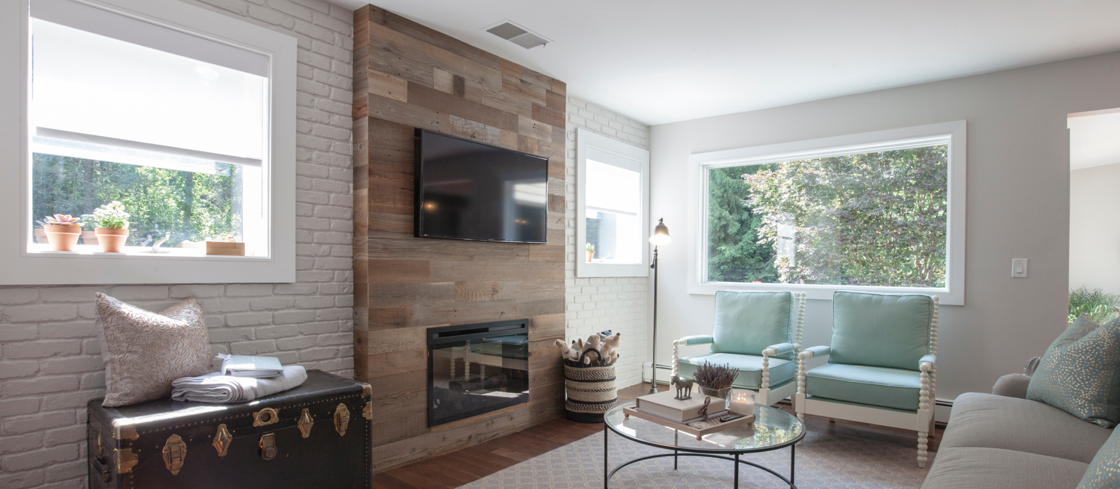 Modern family room with a Stikwood real reclaimed redwood peel and stick wood plank fireplace accent wall with brown, red, silver, gray and gold colors.