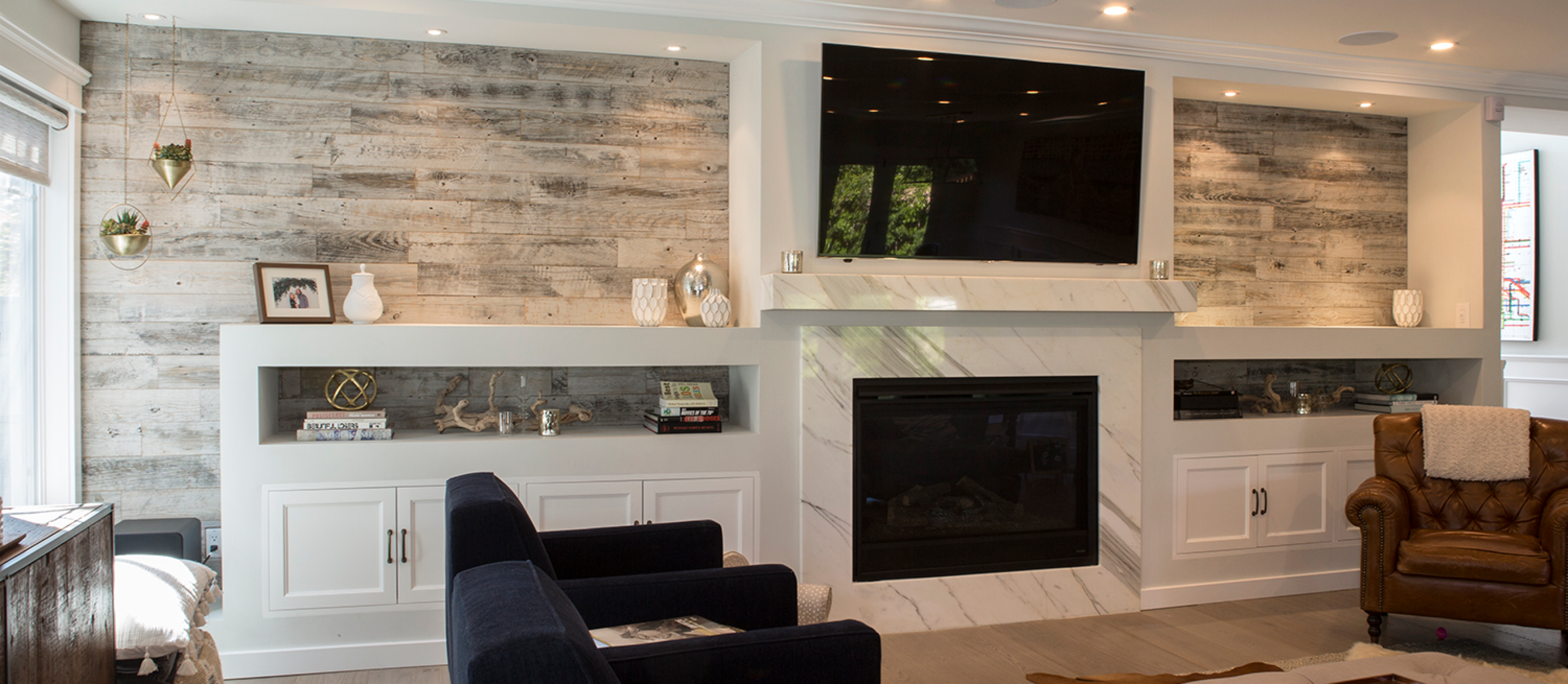 Modern family room with white cabinets and a Stikwood real reclaimed pine peel and stick wood plank accent wall with silver, gray, tan and brown colors.