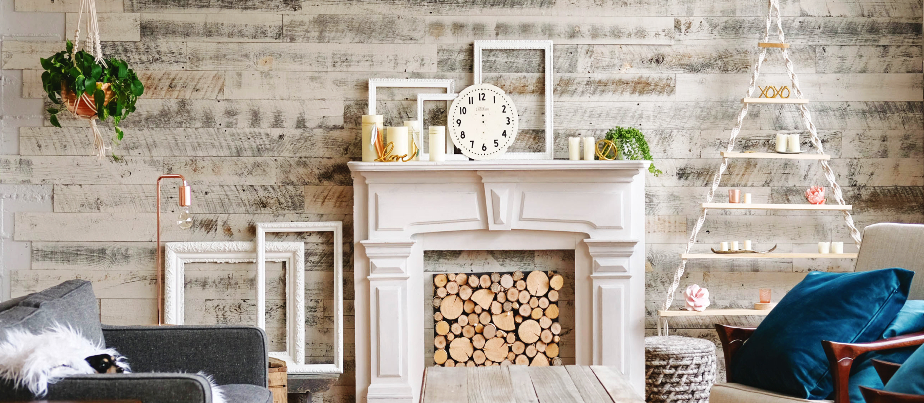 Comfortable living room with fireplace and a Stikwood real reclaimed pine peel and stick wood plank focal wall with silver, gray, tan and brown colors.