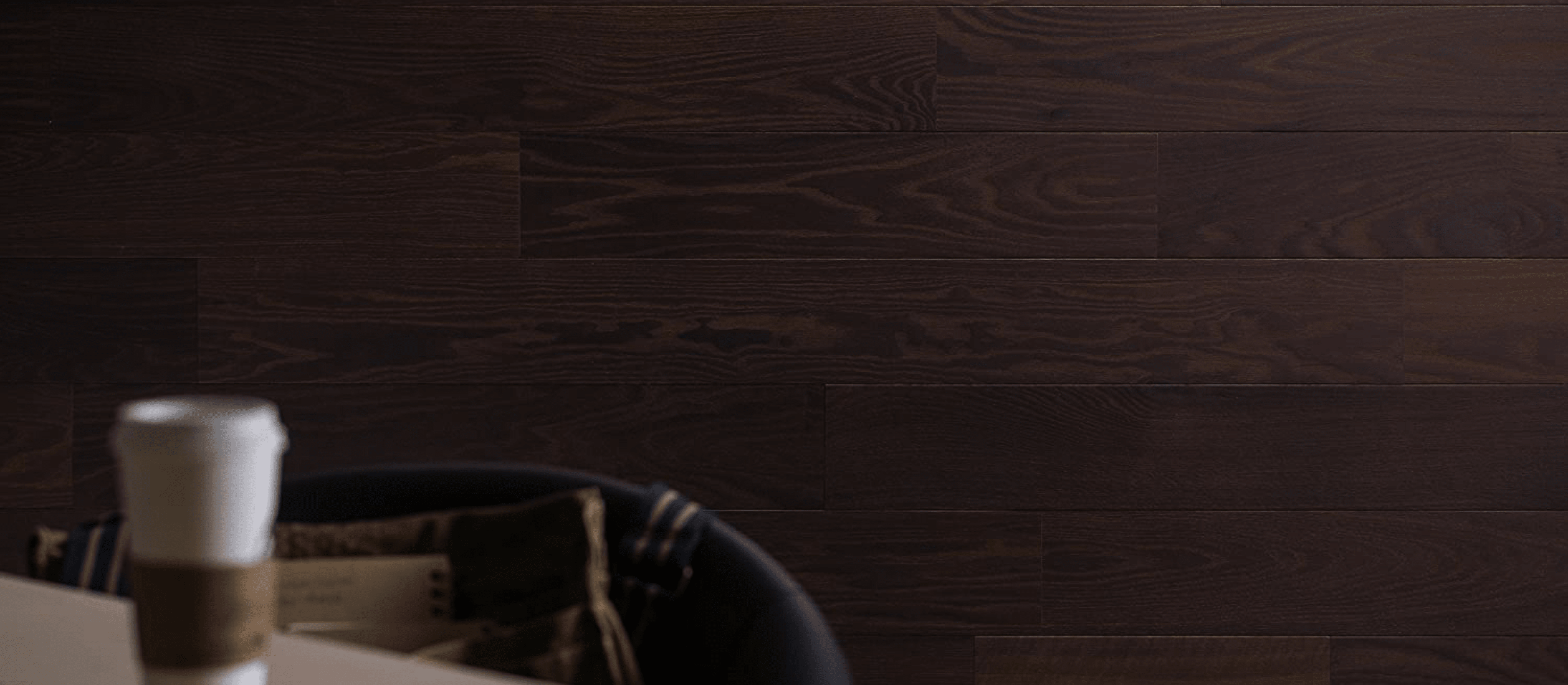 Stikwood Black Cherry peel and stick wall and ceiling planks with dark brown and red colored finish with coffee cup in foreground.