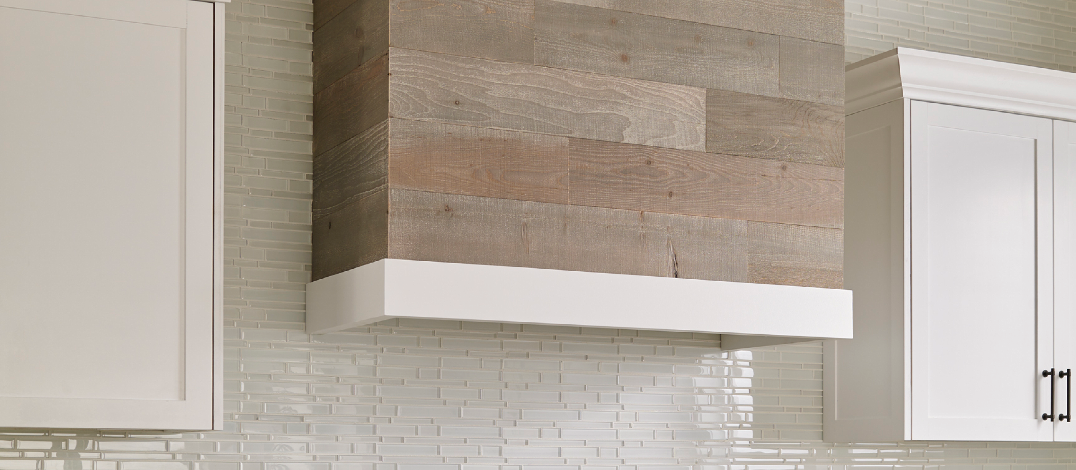 Close-up of a kitchen hood in a classic kitchen with white cabinets and a Stikwood real reclaimed pine peel and stick wood plank accent wall with light, gray, tan, brown colors.