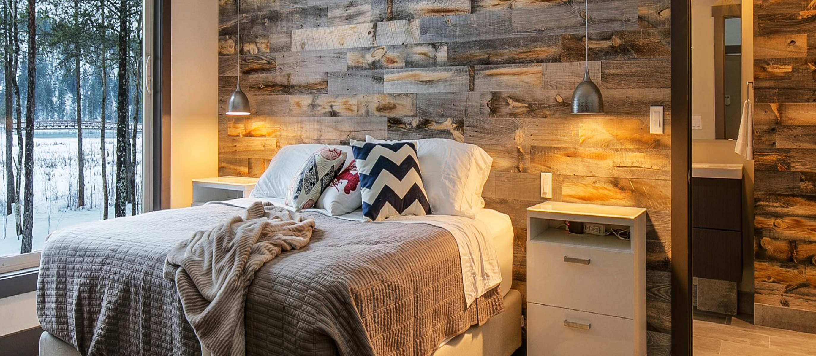 Cabin master bedroom in winter with Stikwood real reclaimed pine peel and stick wood plank accent wall with silver, gray, tan and brown colors.