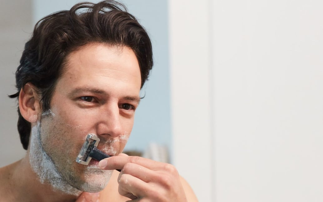A man shaving under his nose with a OneBlade razor