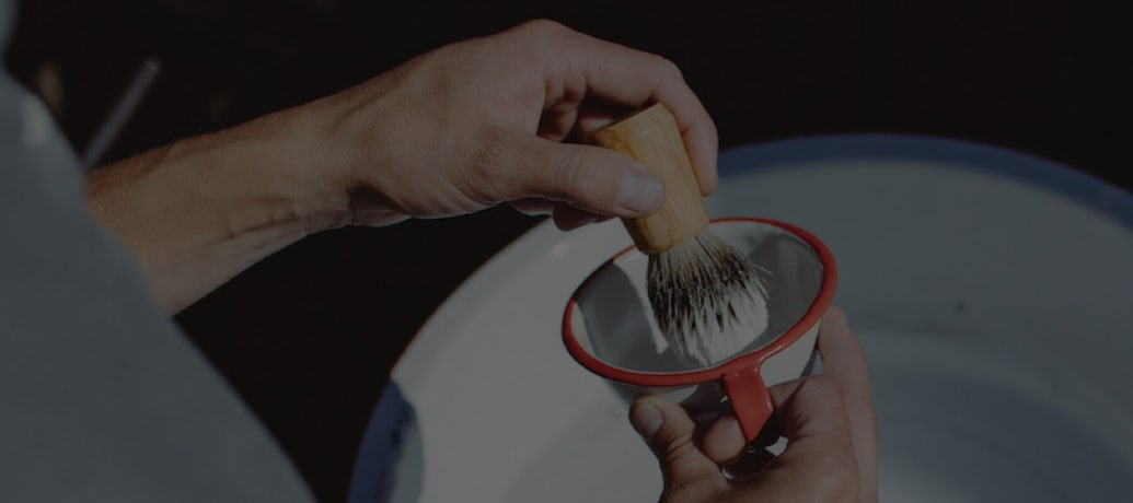A hand dipping a shaving brush into shaving cream