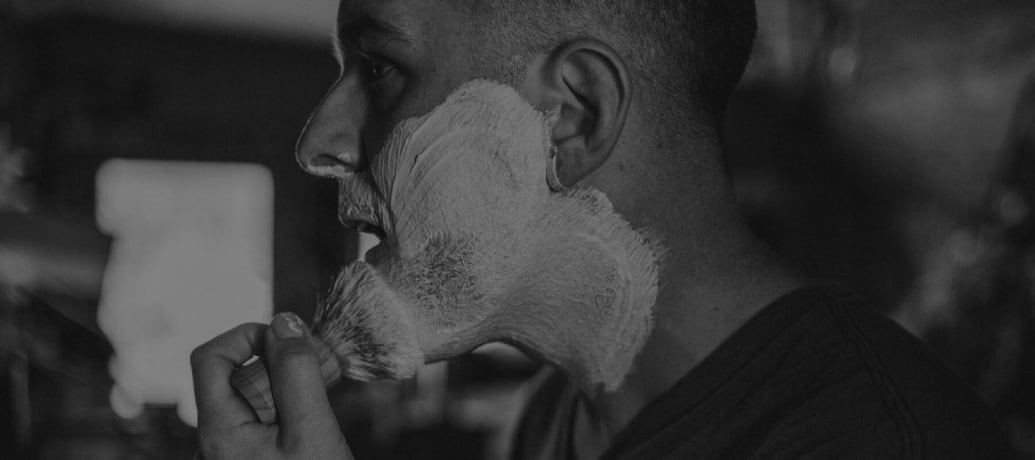 Black and white photo of a man applying shaving cream to his face