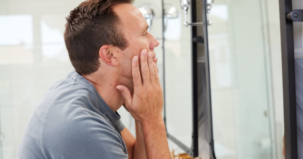 Man looking into a mirror touching his face