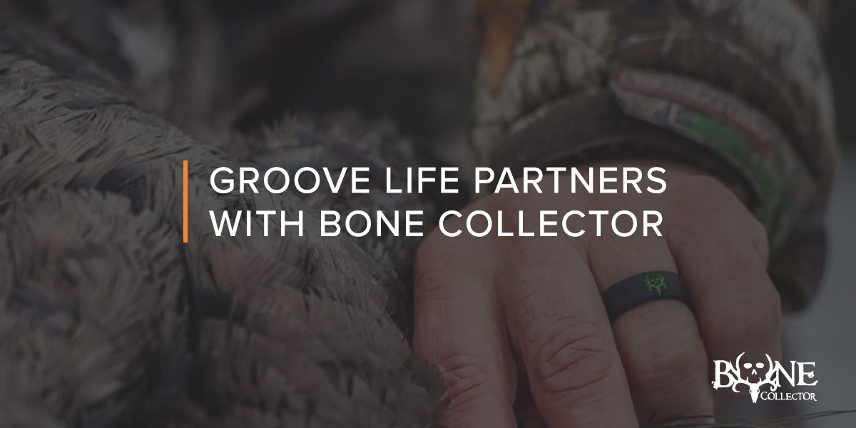 Close up on Bone Collector Black/green ring on hand holding a fluffy blanket