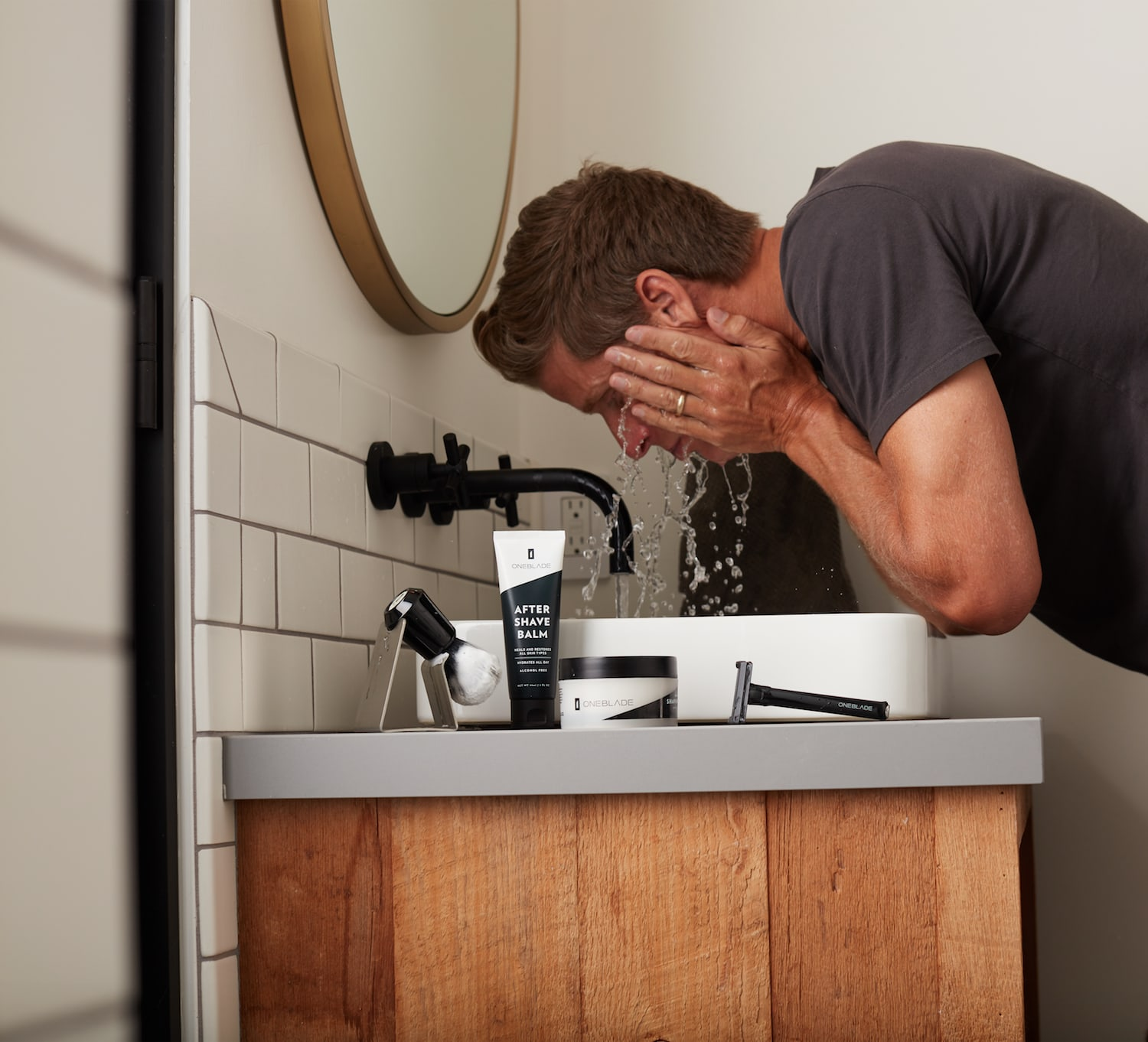 Man splashing water on his face at a sink with OneBlade products sitting