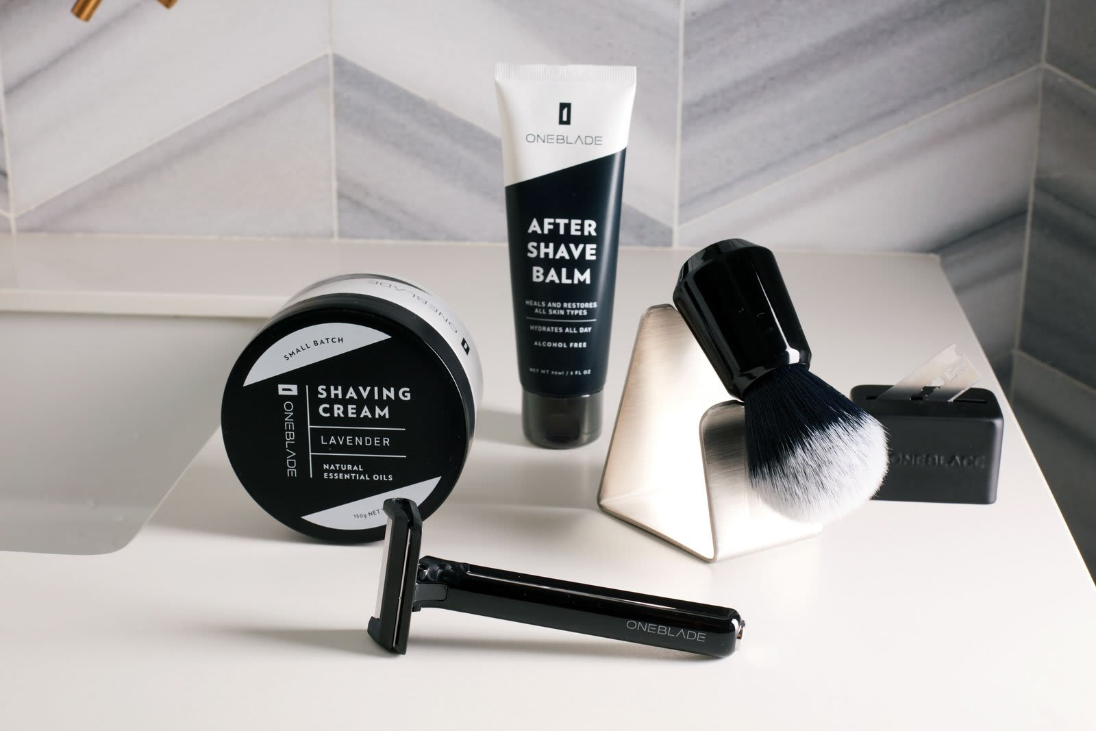 OneBlade Shave Kit, including shaving cream, after shave balm, a shaving brush with stand, a blade disposal box, and a OneBlade razor, all sitting on a countertop.