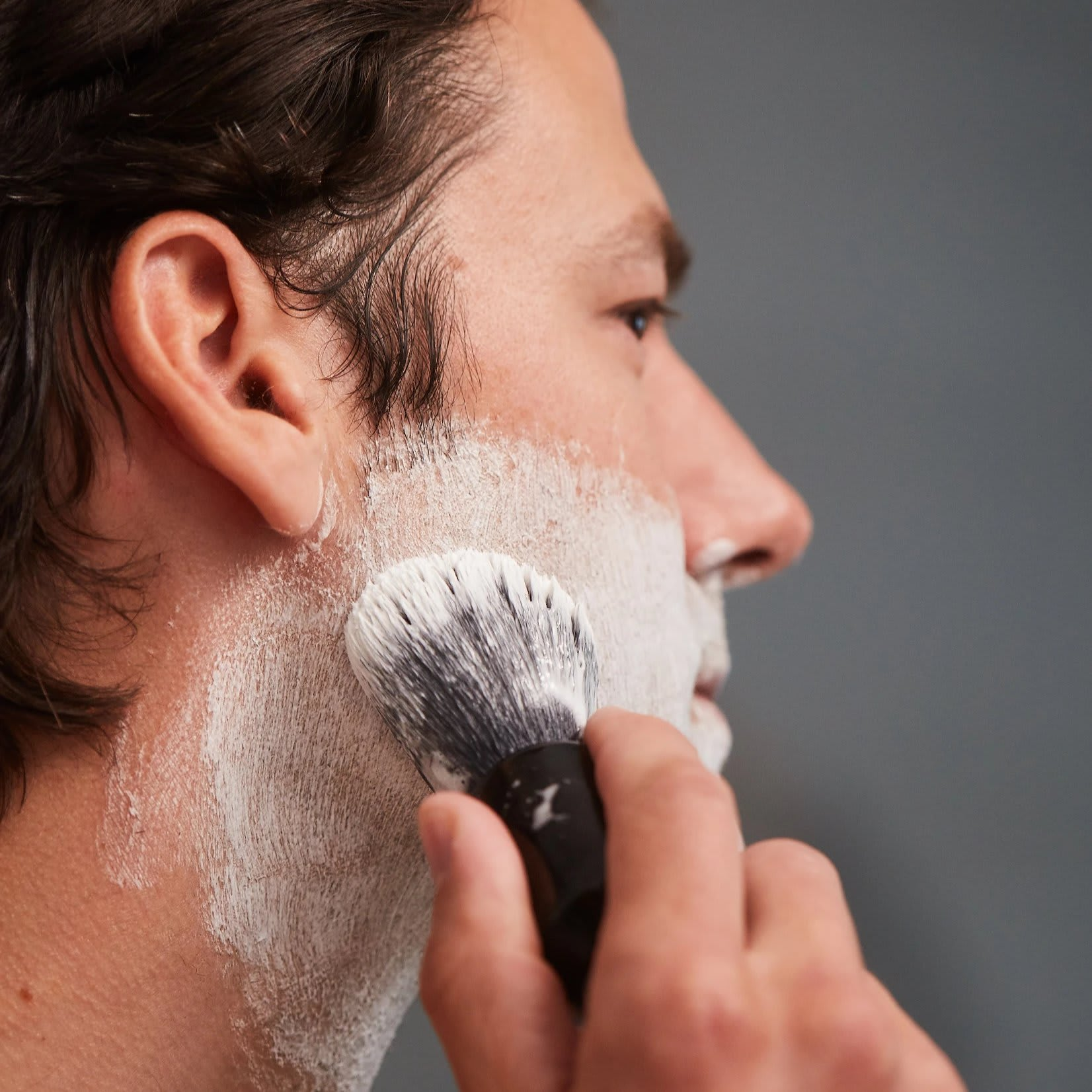 OneBlade shave brush applying shaving cream to face