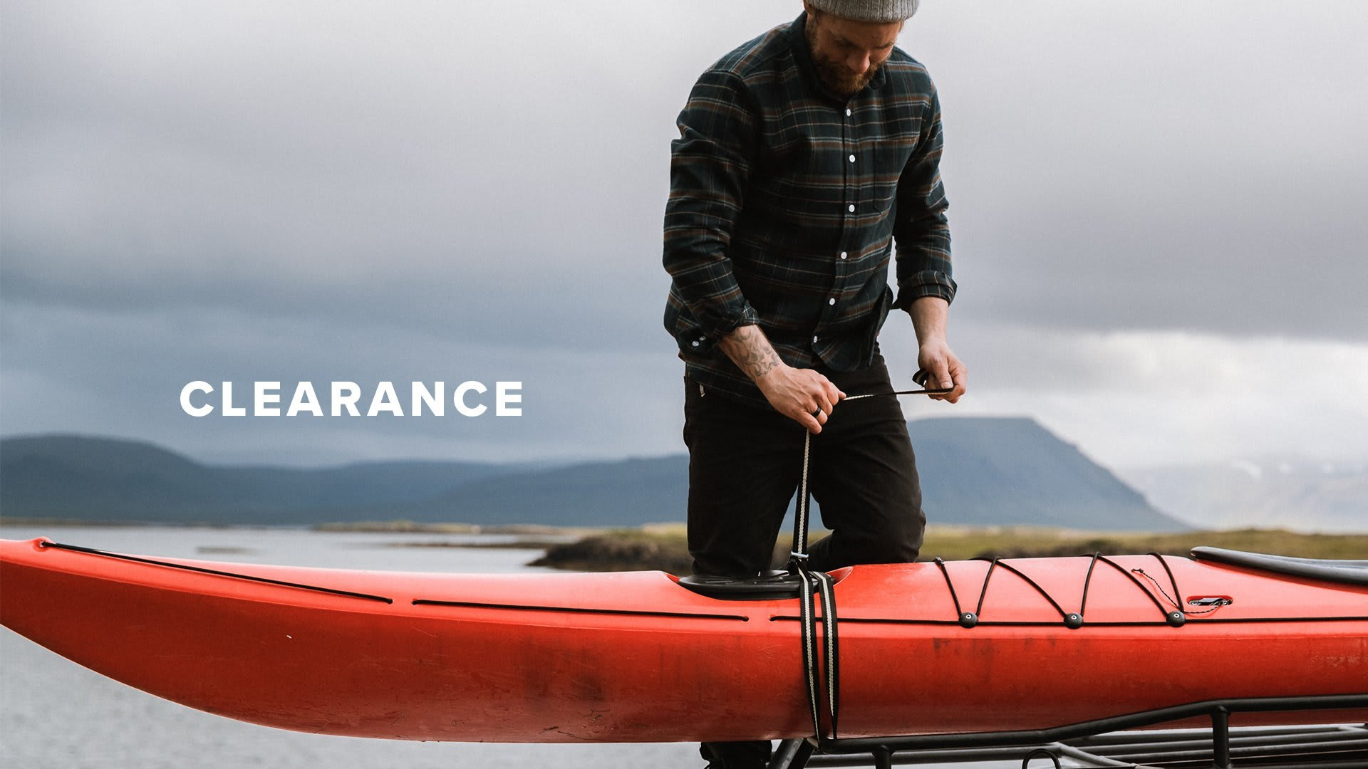 Clearance, man tying down his kayak to a trailer