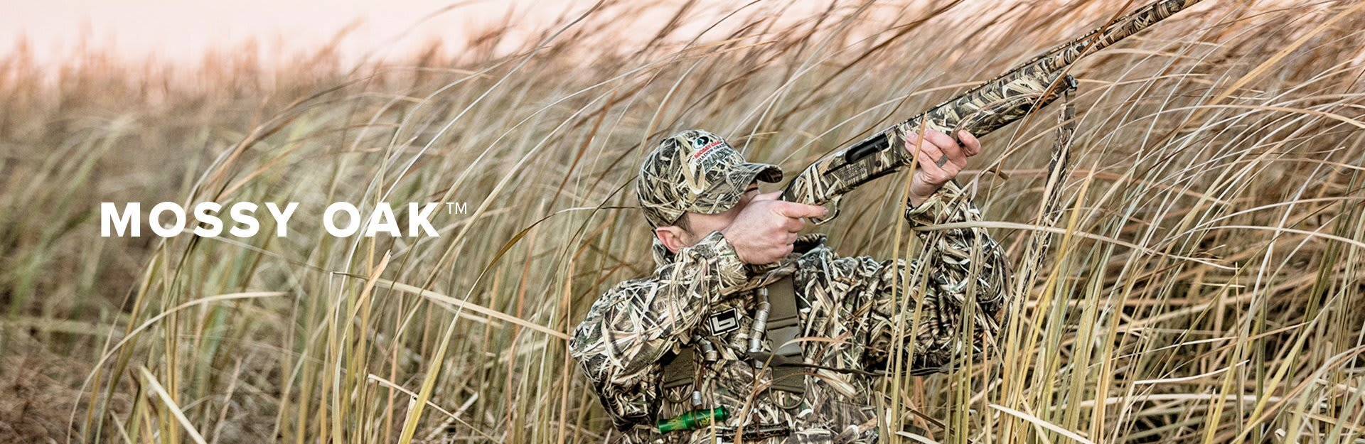 Mossy Oak, a hunter in camo points a shotgun up at some game that is flying