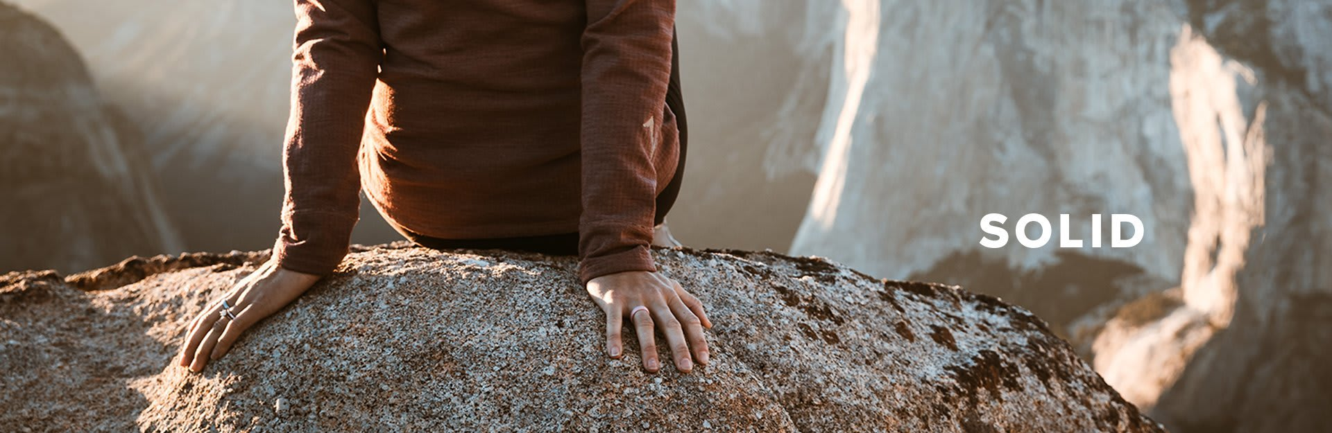 Solid, person sitting on a large boulder