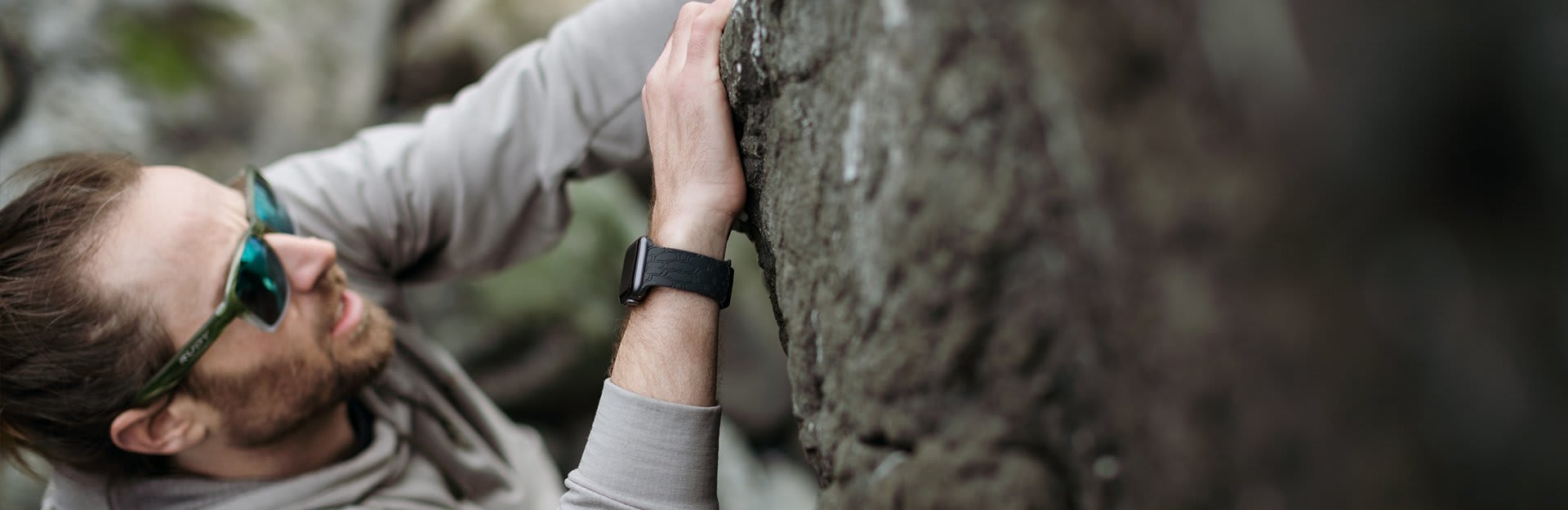 Men's Watch bands, a man wearing sunglasses and a black watch band climbs a rock face