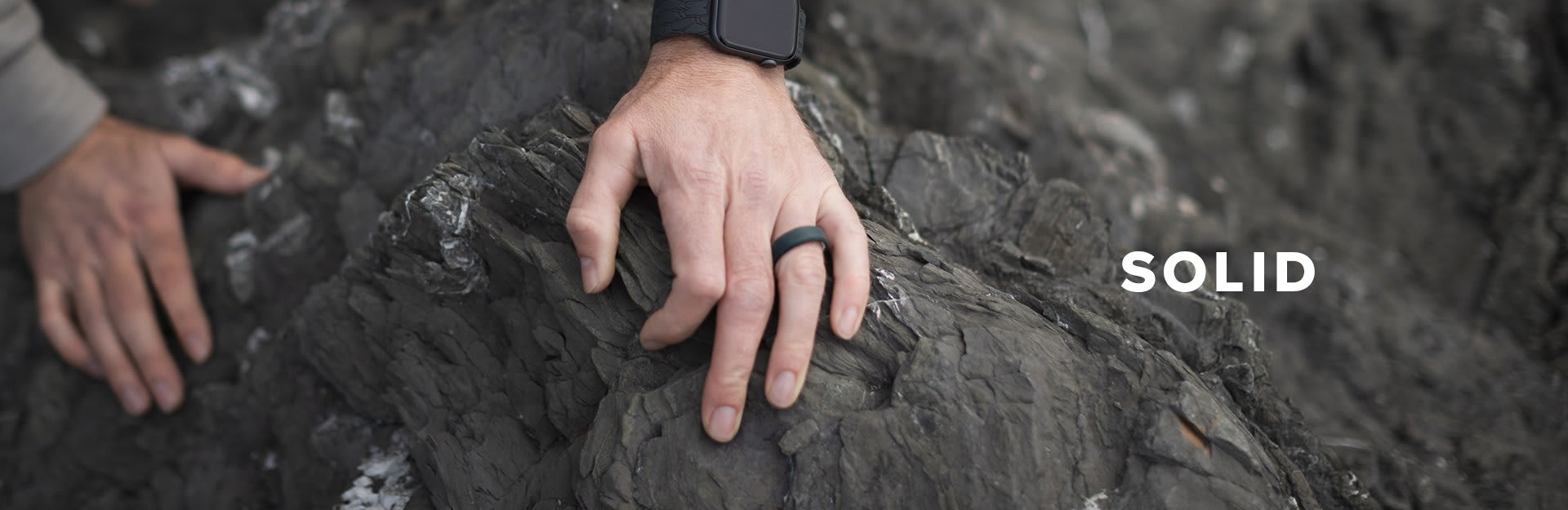 Solid, a man's hand grips a rock and displays his groove ring