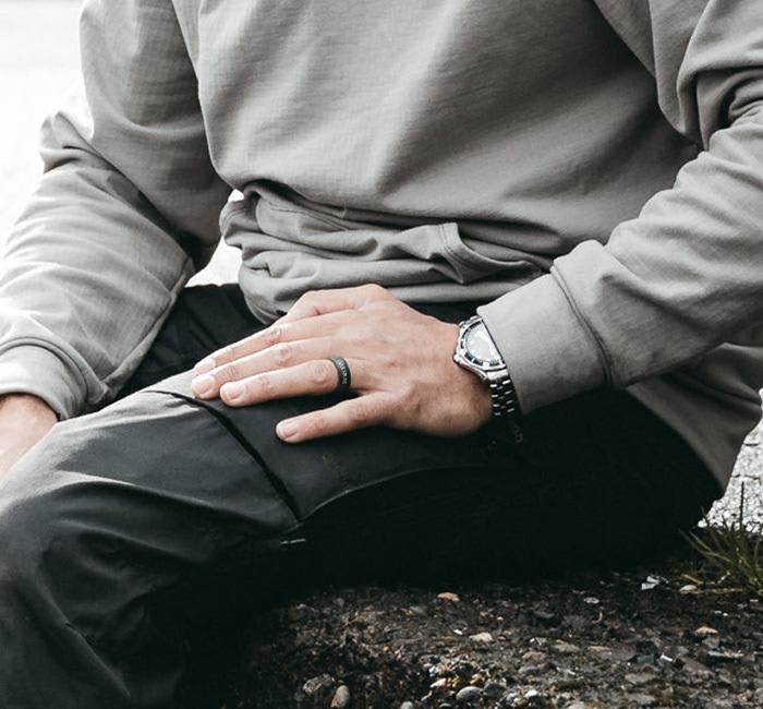 Man sitting on a edge with his personalized ring showing his commitment
