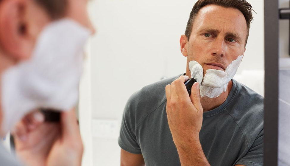 Man looking into a mirror to apply shaving cream to his face with a shave brush