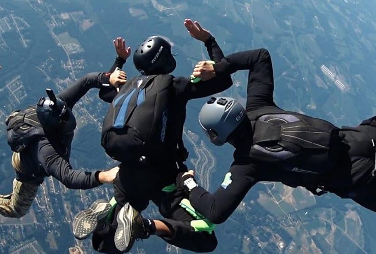 three men in freefall while parachuting