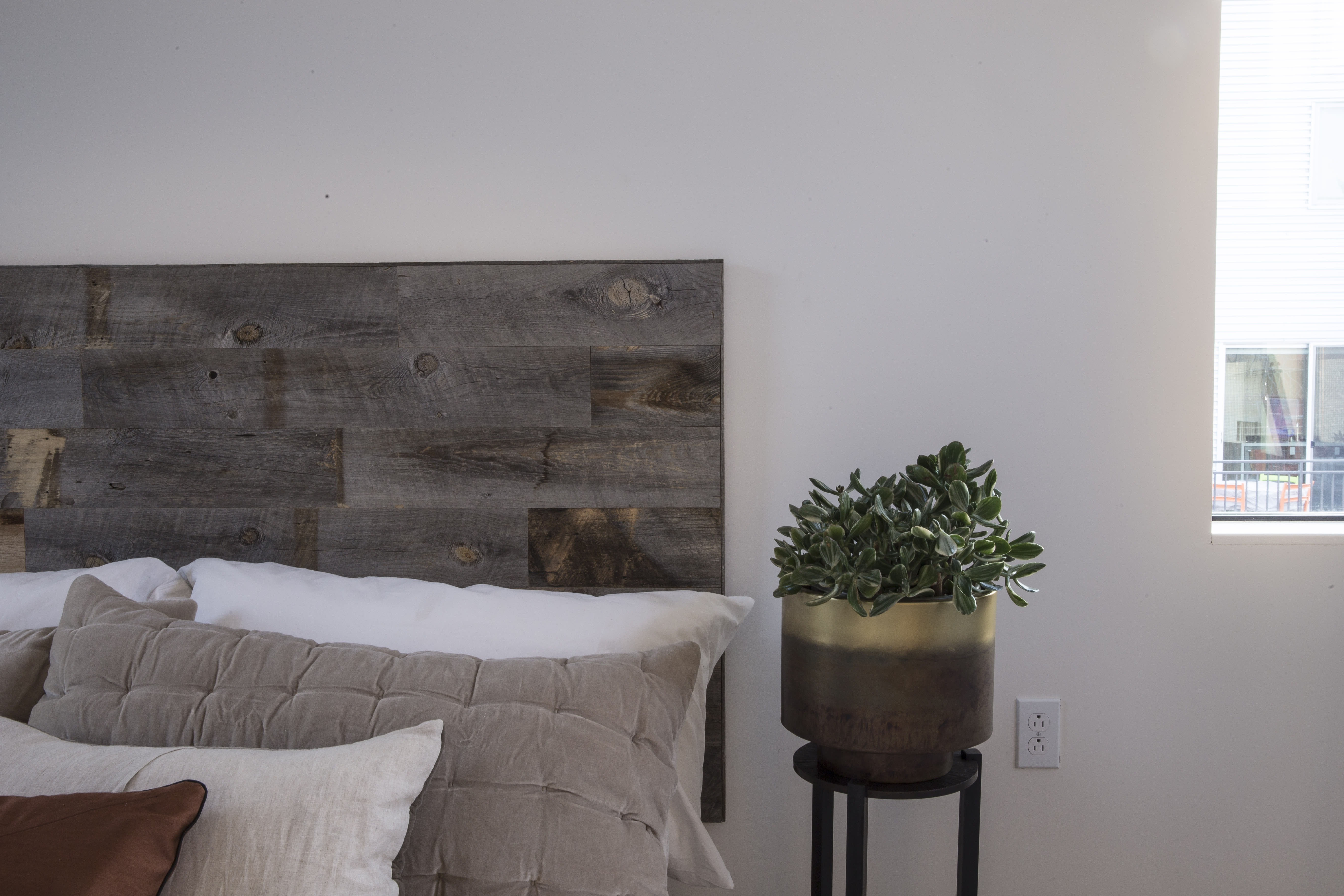 Rustic DIY Reclaimed weathered wood Stikits headboard kit assembled and attached to wall behind nicely decorated bed.