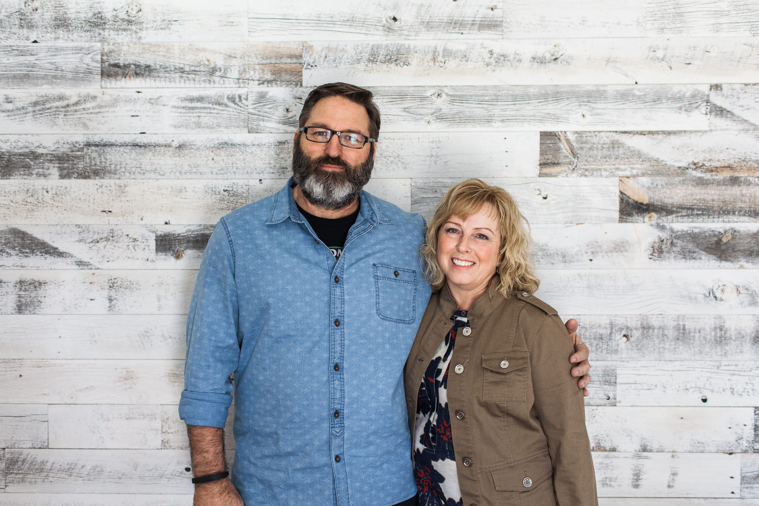 Laura and Jerry McCall the creators of peel and stick real wood for your walls and ceilings standing in front of reclaimed wood accent wall.