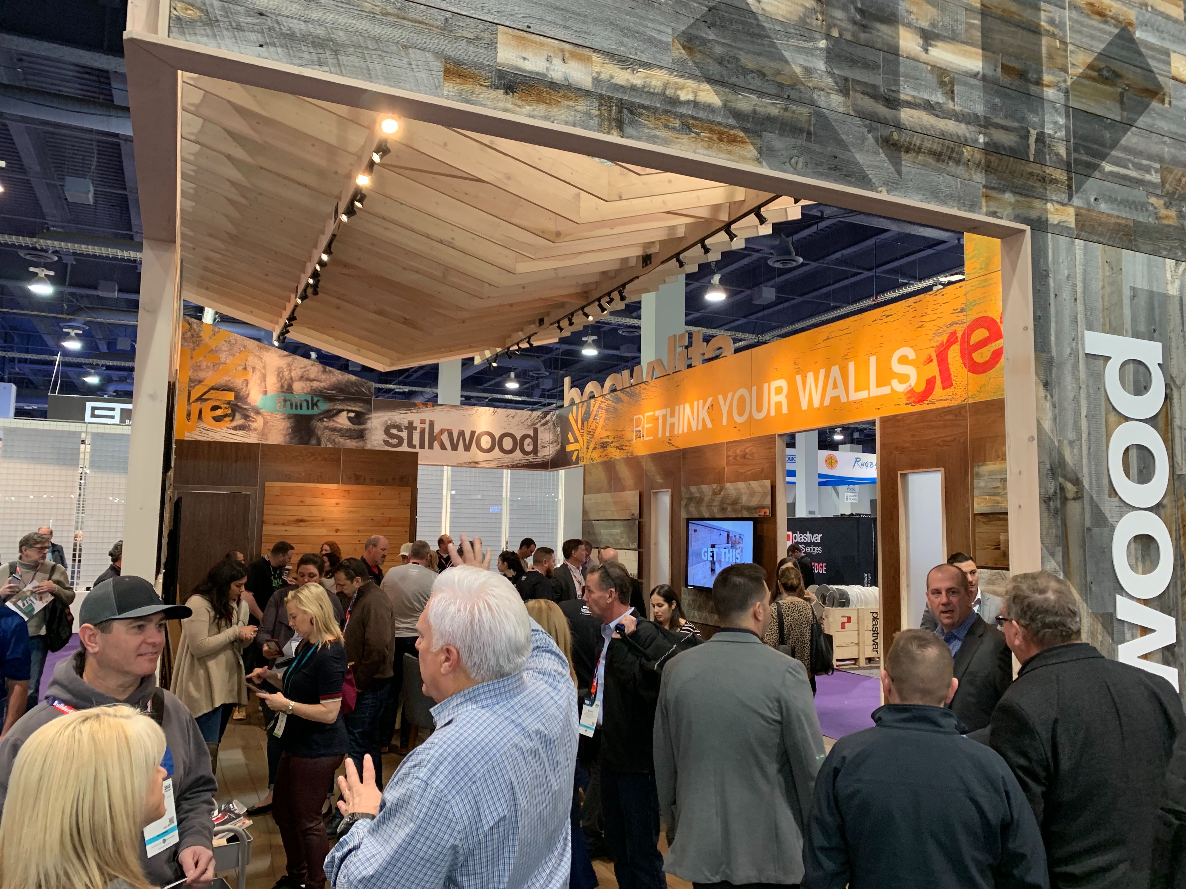 Stikwood's 2018 KBIS conference booth showing the booth interior and customers exploring peel and stick wood planks.