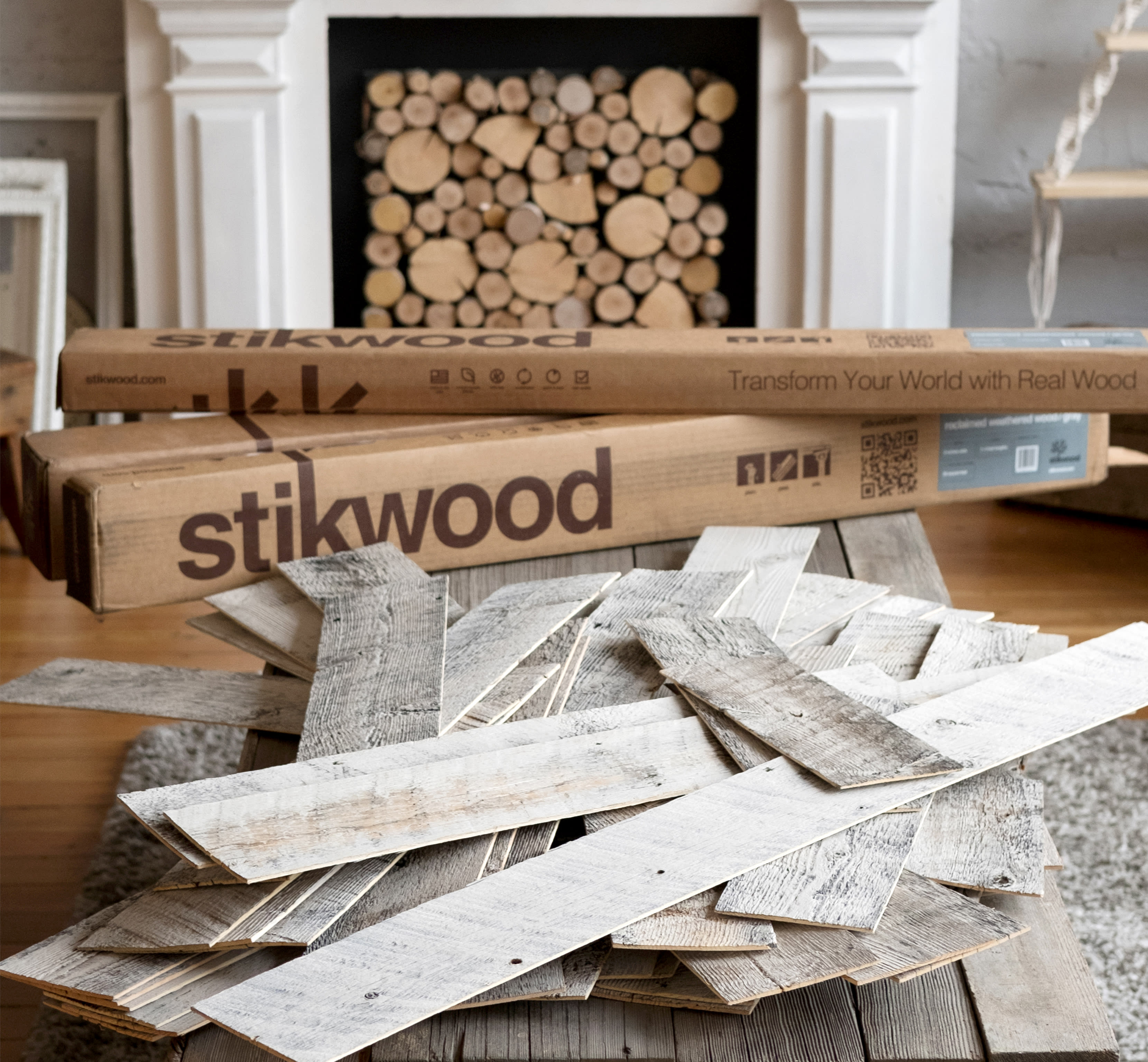 Living room fireplace filled with wood and a pile of stikwood reclaimed weathered wood gray peel and stick wood planks out front acclimating.