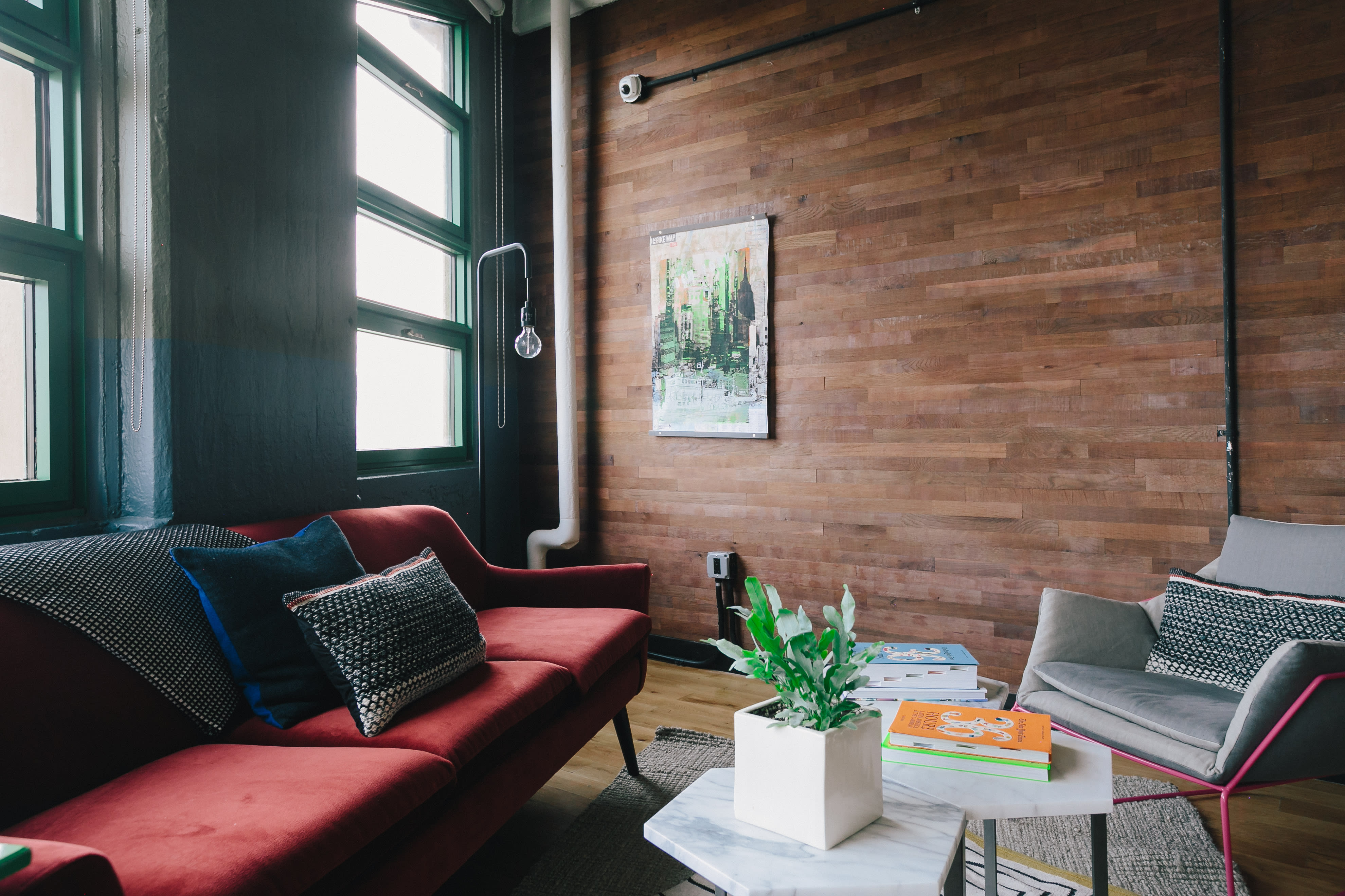 Modern loft apartment living room with contemporary furniture and a large Stikwood peel and stick wood accent wall in Reclaimed Barrel Oak plank finish.