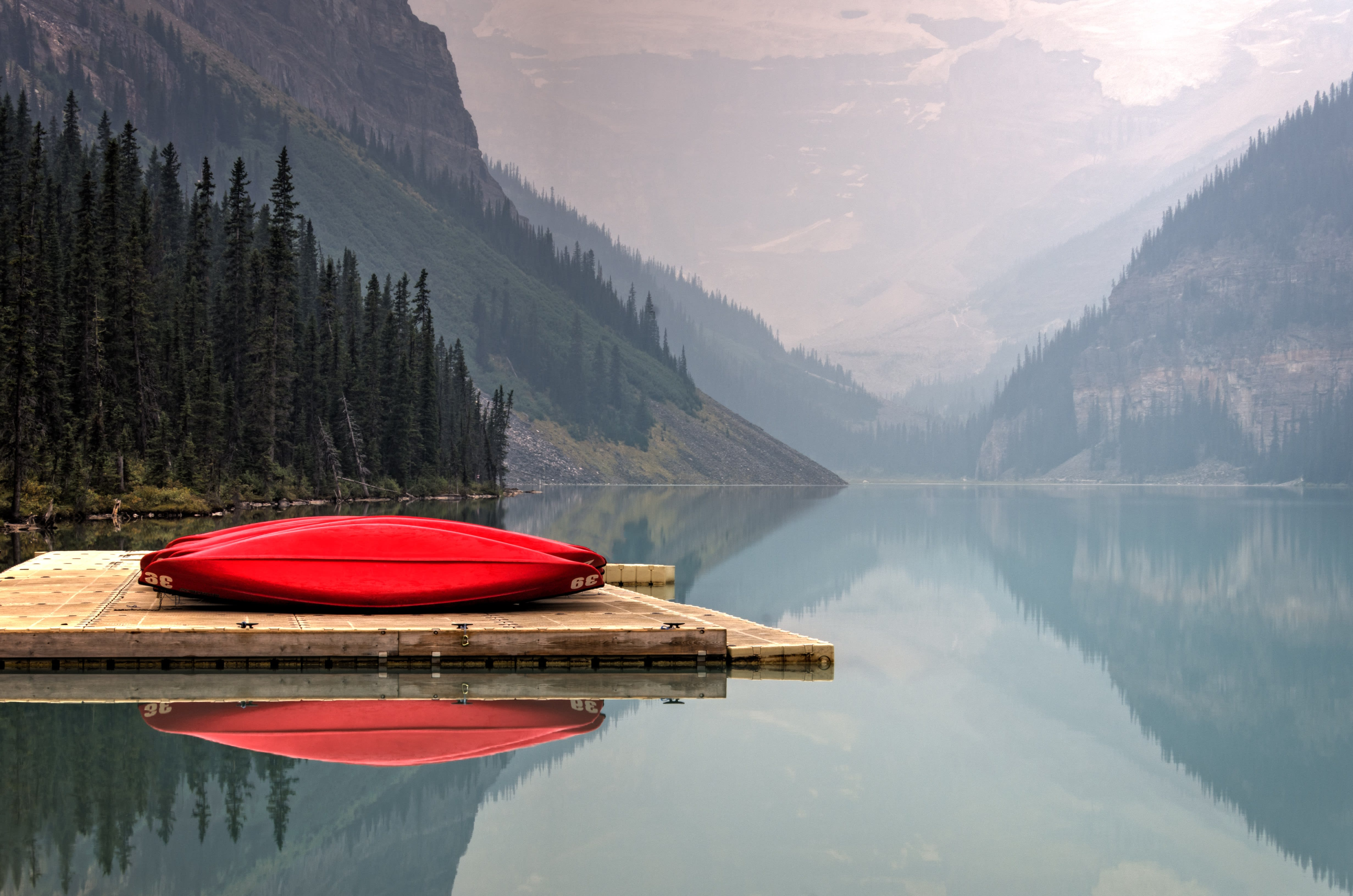Canoe on dock by a calm mountain lake.