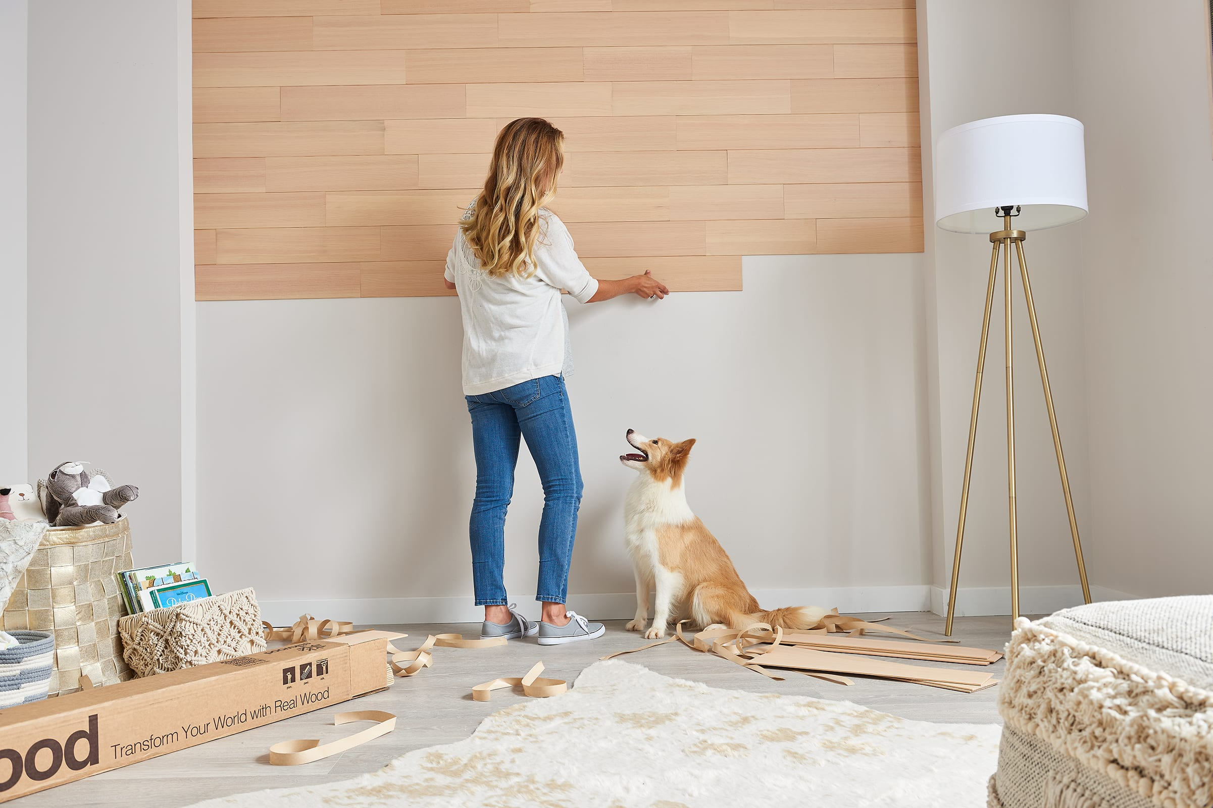 Pregnant woman and her dog preparing a nursery by installing vertical grain natural wood wall planks on an accent wall.