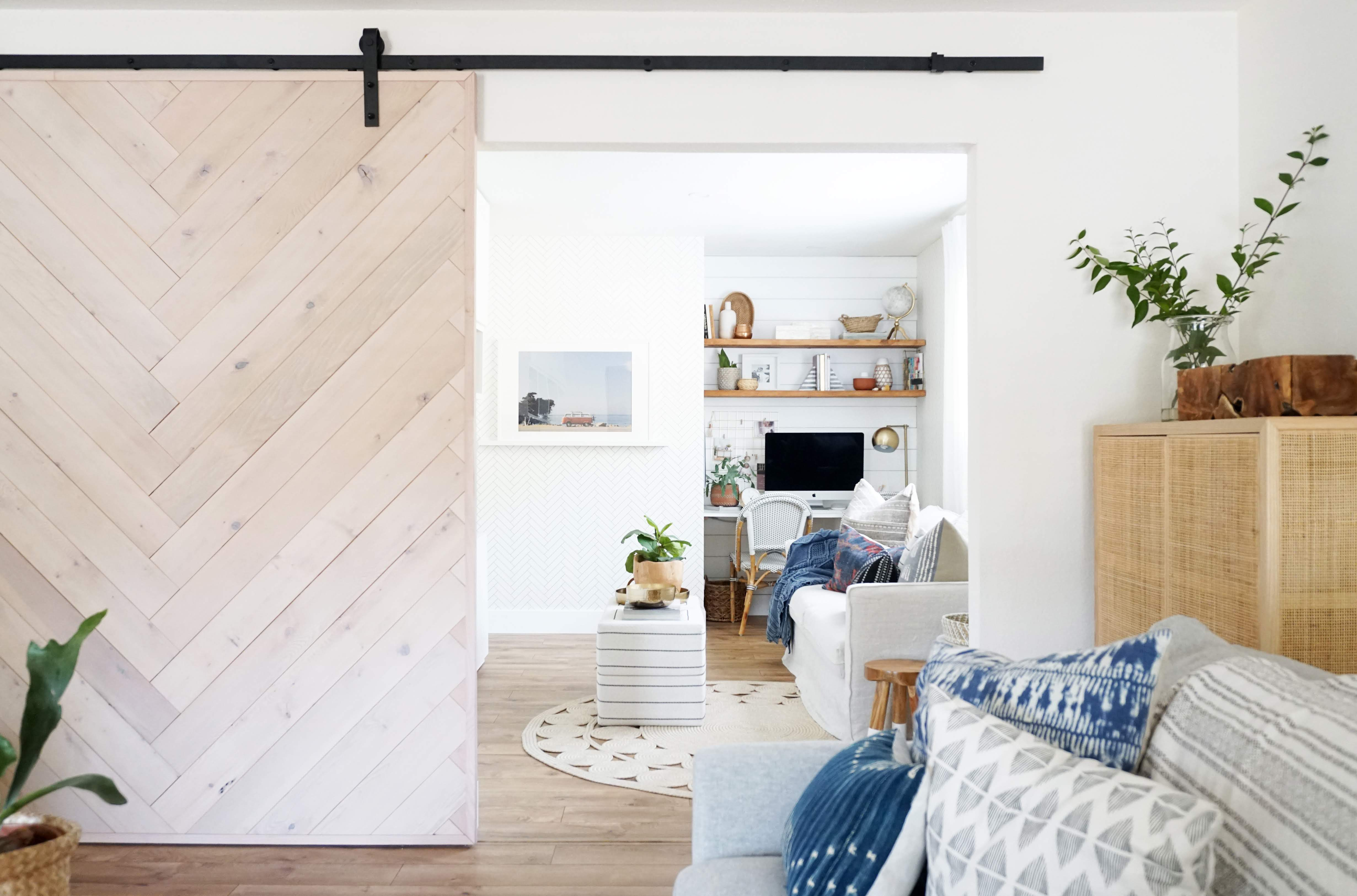 Large open barn door in master bedroom wrapped in angled patterned minimalist fir peel and stick wood wall planks.