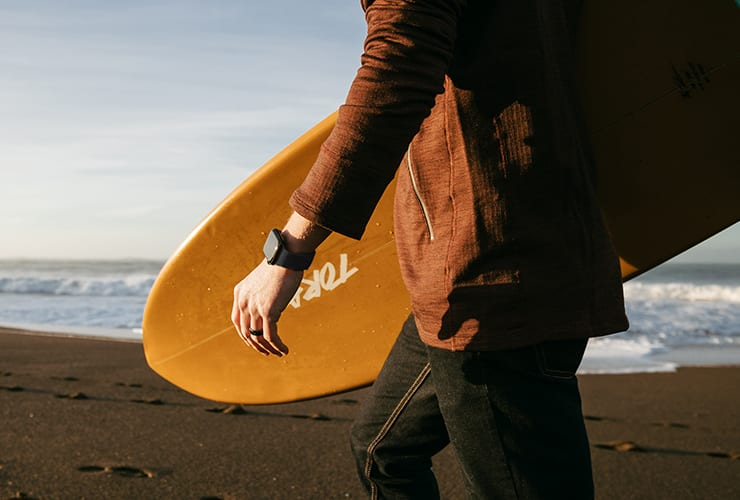 Man walking towards a beach holding a surfboard under his arm